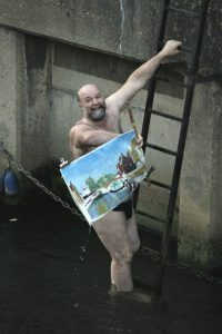 Artist John Behm dives in River Wensum from Fye Bridge to save another artist's painting. Photo © Katy Jon Went