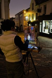Artist Emily Faludy painting on London St by night, Paint Out Norwich 2017. Photo © Katy Jon Went