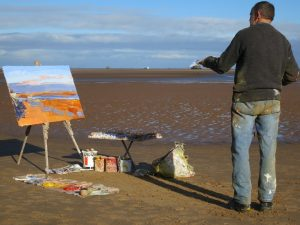 Artist George Rowlett painting plein air on the beach at Humberston