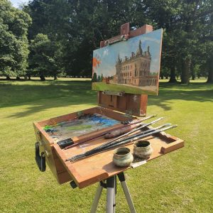 The easel of artist Robert Nelmes painting Houghton Hall at Paint Out Norfolk 2019