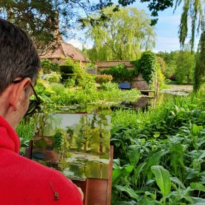 Artist Robert Nelmes painting plein air at Paint Out Elsing Hall Gardens, Norfolk