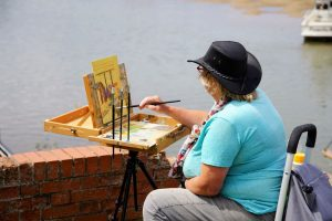 Artist Amanda Barrett painting on Wells-next-the-Sea quayside at Paint Out Norfolk 2020