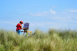 Artist Karen Adams painting on Winterton Beach dunes during Paint Out Norfolk 2020